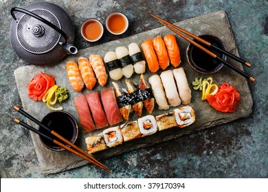 Sushi Set nigiri and sushi rolls with tea served on gray stone slate on metal background
