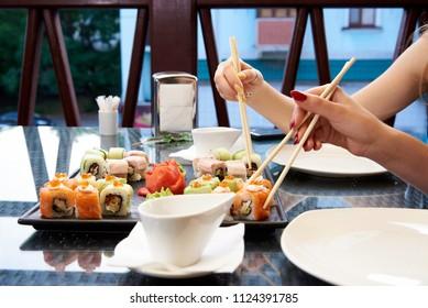 Sushi set on a glass table.  Girls eating sushi rolls using bamboo sticks.