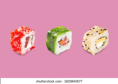 sushi set on a pink background. different sushi stuffed with fish, rice, cheese, and avocado.