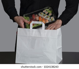 Sushi set on plastic container ready to take away on white bag.