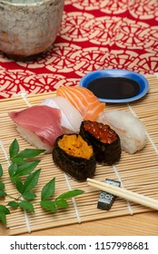 sushi set on white bamboo sheet with chopsticks and soy sauce vertical version