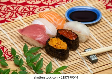 sushi set on white bamboo sheet with chopsticks and soy sauce