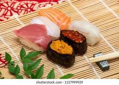 sushi set on white bamboo sheet with chopsticks