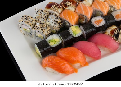 Sushi set on a white plate over black background