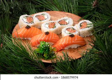 Sushi set on a wooden plate with fir branches on the background. Christmas and New Year celebration table. Philadelphia maki roll, sashimi nigiri with salmon and wakame salad. Side view, close up
