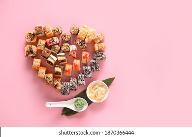 Sushi set in plate as heart served ginger, wasabi on pink background. Valentine day food concept. View from above. Space for text. Flatlay style.