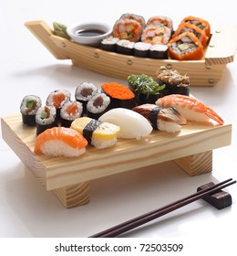 sushi set and sushi roll on wooden board