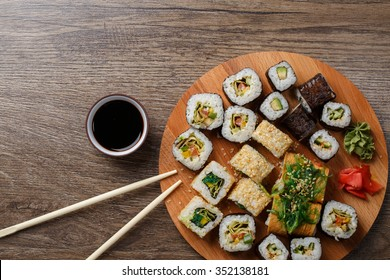 Sushi set at round wooden plate on wooden table