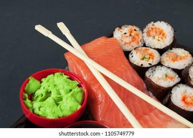 Sushi Set sashimi and sushi rolls with red fish and wasabi on black background