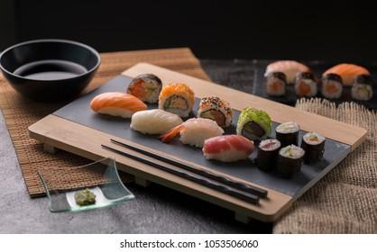 Sashimi et rouleaux de sushi de l'ensemble de sushis servis sur ardoise en pierre