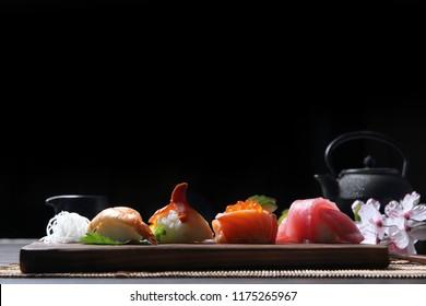 Sushi Set sashimi and sushi rolls with tea on wood background