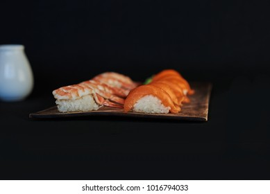Sushi set sashimi  served on wooden plate. Sashimi  with salmon, eel, tuna, avocado, royal prawn, cream cheese caviar tobiko, chuka. Sushi menu. Japanese food. Selective focus. Black background.