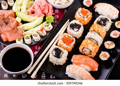 Sushi set, soy sauce, ginger, wasabi, black and red roe, avocado, salmon, cheese on background