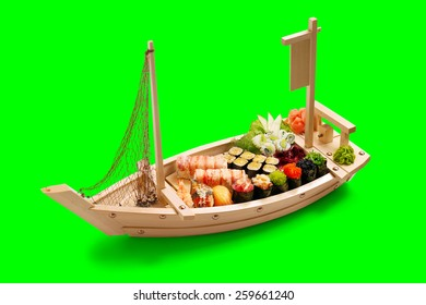 Sushi set in the wooden ship. Isolated on green background