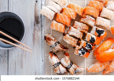 Sushi and soy sauce in a bowl and wooden chopsticks on a gray wooden table. Japanese food. Sushi Set. Variety of rolls. Menu.