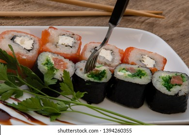 Sushi strung with a fork, Japanese rolls, fish and rice