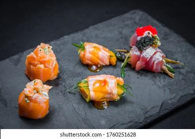 Sushi, traditional Japanese cuisine. Several delicious sushi on the decorated plate, black background. Group of sushi, Urakami, Nigori, Sushi jow, sashimi, tekamaki, etc ...