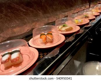 Sushi tray on conveyor belt in restaurant (Selective Focus)