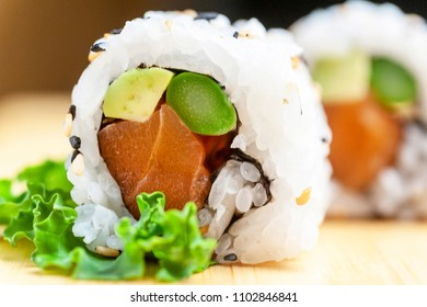 Sushi Uramaki de arroz con atun, aguacate y esparragos trigueros sobre base de madera clara y fondo oscuro