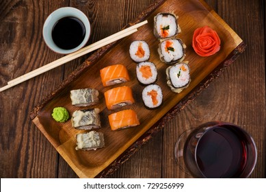sushi and wine on wooden table, top view