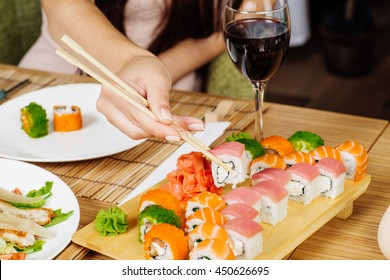 Sushi. Woman hand with Japanese sticks.. Sushi set at plate on wood table.