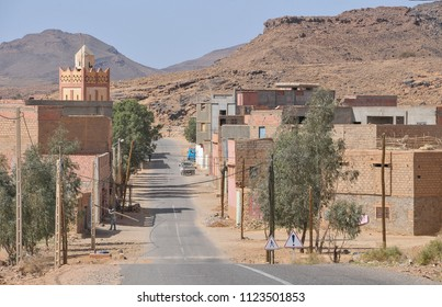 Sus-Masa-Draa, Morocco - march 20, 2012: Rural road and village with houses and mosque built on the edges of the road, in the Zagora region