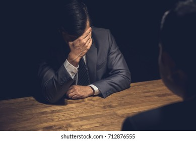 Suspect businessman displaying regret, worry and concern using body language in dark interrogation room