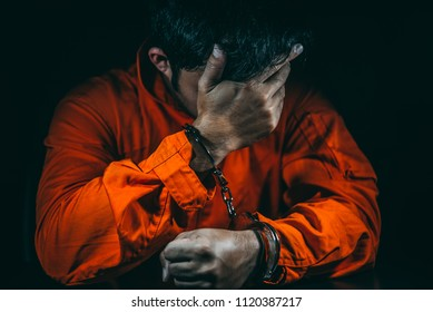 The suspect wear prisoner cloths was arrested at the investigation, interview to find out the truth, the thief was caught by the police come to the dark room,Thailand people,Knife in hand