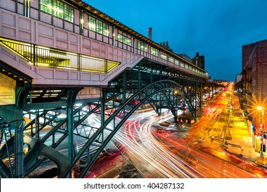 Suspended 125th Street Metro-North Railroad commuter rail hub station, in Harlem, New York City. Rush hour traffic leaves light trails on Broadway.