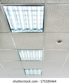 Suspended ceiling with fluorescent lighting and smoke detectors