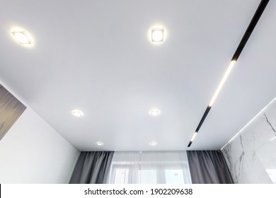 suspended ceiling with halogen spots lamps and drywall construction in empty room in apartment or house. Stretch ceiling white and complex shape.