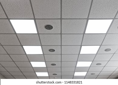 Suspended ceiling with LED square lamps and round speakers in the conference room.