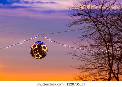 Suspended christmas street lights at sunset