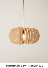 Suspended wooden lamp isolated on a brown background. Modern chandelier of wood in Scandinavian style