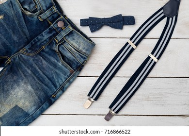 suspenders and bow tie on wooden background. Kids fashion.