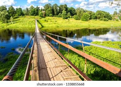 Suspension bridge across the Msta river in summer day in Borovichi, Russia