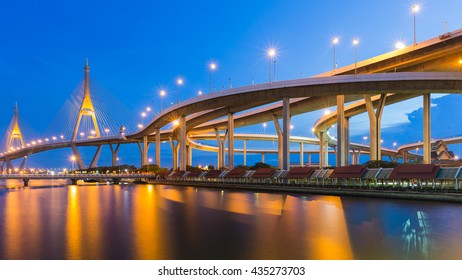 Suspension Bridge connect to highway river front and reflection lights, night view, Thailand Landmark