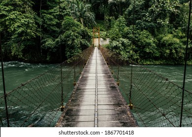 Suspension Bridge crossing the world famous clear water rapid of Asahan River surrounded by dense rainforest is perfect for kayak and white water rafting, North Sumatra, Indonesia.