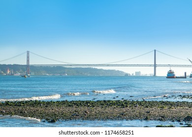 Suspension Bridge in Lisbon, Portugal. Connects the cities of Lisbon and Almada crossing the Tagus River. Evening photo.