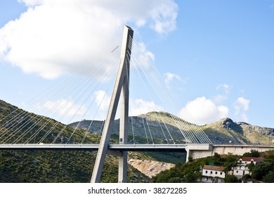 A suspension bridge on green hills against blue sky