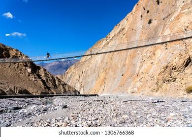 Suspension bridge on a popular tourist destination trail - Annapurna Circuit Trail in Nepal, Himalaya mountains.