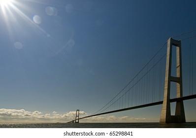 Suspension bridge on the sea with backlight