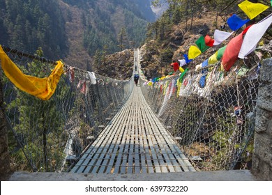 Suspension bridge over the precipice with colorful flags in nepal in  green forest and hills.