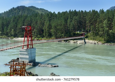 Suspension bridge over river Katun in village Barangol. Altai Republic, Siberia. Russia