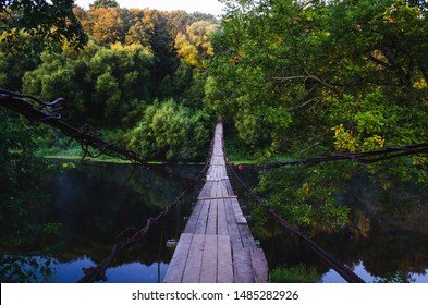 Suspension bridge over the river. Wooden suspension bridge in the summer in the village of Khotylevo, Bryansk