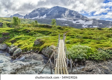 Suspension bridge over rough mountain river in the Hardangervidda National park in Norway. Summer season. Trekking trail in norwegian mountains.
