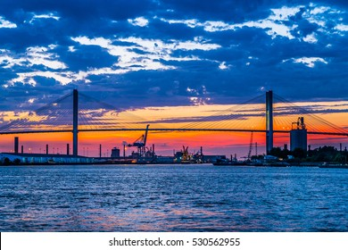 Suspension bridge over the Savannah River at sunset with a view of the harbor.
