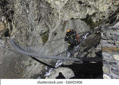 a suspension bridge with porter carrying duffle bags on Annapurna circuit trek in Himalayas, Nepal