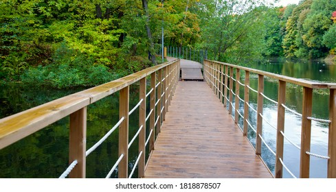Suspension bridge and walking wooden path over the lake on an autumn evening