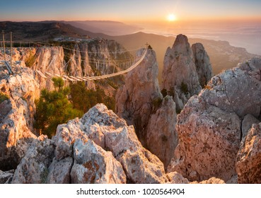 Suspension bridges high in the mountains on the background of the rising sun